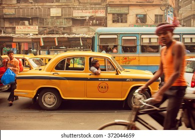 KOLKATA, INDIA - JAN 13: Yellow taxi car, buses and cyclists driving on the busy street of indian city on January 13, 2013 in Calcutta. Kolkata has a density of 814.80 vehicles per km road length