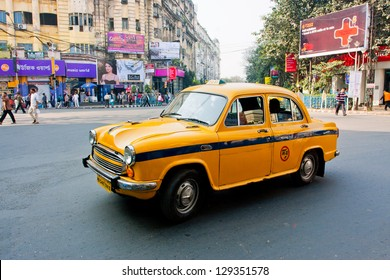 KOLKATA, INDIA - JAN 17: Yellow Ambassador taxi car goes through the indian street on  January 17 2013 in Kolkata, India. First Ambassador was produced by the Yellow Cab Manufacturing Company in 1921