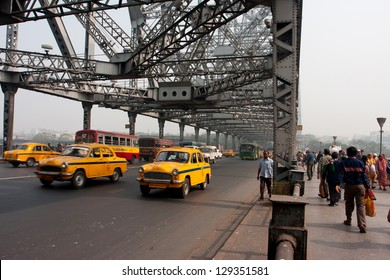 KOLKATA, INDIA - JAN 18: Yellow Ambassador taxi cabs goes on the Howrah bridge on January 18 2013 in Kolkata, India. Hindustan Ambassador is a car manufactured by Hindustan Motors of India since 1958