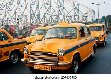 KOLKATA, INDIA - JAN 19: Yellow taxi cabs stop in traffic jam street with metal bridge background on January 19, 2013 in Kolkata, India. Kolkata has a density of 814.80 vehicles per km road length