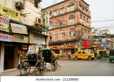 KOLKATA, INDIA - JAN 20: Bicycle rickshaw stops on the street corner with a traffic on the busy city street on January 20, 2013 in Calcutta. Kolkata has a density of 814.80 vehicles per km road length