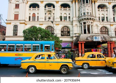 KOLKATA, INDIA - JAN 22: Colorful taxi cabs drive faster of real speed limit on the busy street of city on January 22, 2013 in Calcutta. Kolkata has a density of 814.80 vehicles per km road length