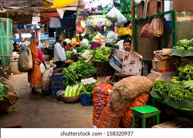 KOLKATA, INDIA - JANUARY 10: Vegetable seller reads a newspaper and waits for the customers on the old city market on January 10, 2012 in Calcutta. 0.81% of Kolkata's workforce employed in agriculture
