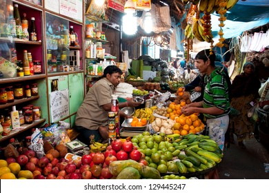 KOLKATA, INDIA - JANUARY 16: Customer buys fruit in the colorful city market on January 16, 2012 in Kolkata India. Only 0.81% of the Kolkata's workforce employed in the primary sector (agriculture)