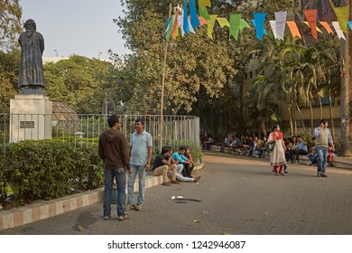 Kolkata, India, January 2016 People talking and walking in a park next to a sculpture by Rabindranath Tagore.