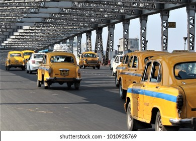 Kolkata, India - January 29, 2017:  Classical yellow ambassadors taxis are seen passing through the iconic Howrah Bridge on Hoogly river in Kolkata.