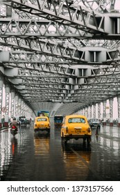 KOLKATA, INDIA. JUL 23, 2017: Yellow taxis running on the road inside Howrah Bridge in the afternoon with rain in Kolkata, India.