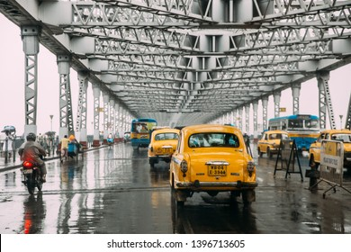KOLKATA, INDIA. JUL 23, 2017: Yellow taxis and motorcycles are running on the road inside Howrah Bridge in the afternoon with rain in Kolkata, India.