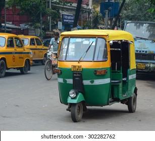 KOLKATA, INDIA - JUL 8, 2015. Private auto rickshaw three-weeler tuk-tuk taxi drives down the street in Kolkata. Indian three-wheelers have the design of the Piaggio Ape C, from 1948.