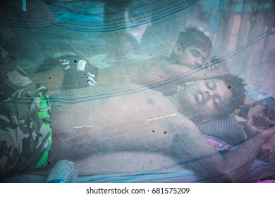 KOLKATA, INDIA - JULY 15, 2017:  A young man is homeless and sleeping outdoor on the Streets while protecting himself with a mosquito nett