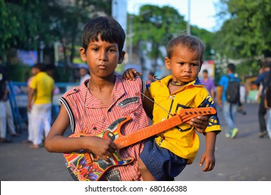 Kolkata, India - July 16, 2017: Street children playing guitar in the road.