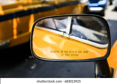 KOLKATA, INDIA - JULY 16, 2017: An inscription of the side mirror of an indian yellow taxi saying Objects in the mirror are exactly as they appear