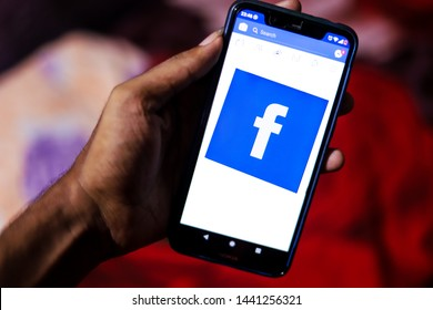 KOLKATA, INDIA - JULY 3, 2019: Hand holds a smartphone with Facebook  logo on the scrren. Server of Famous social media website facebook gets down at the evening of 3rd july 2019 in India and world.