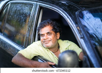 KOLKATA, INDIA - JUNE 26, 2017: An Indian male driver is hanging outside his black car