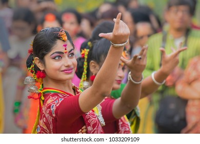 KOLKATA , INDIA - MARCH 12, 2017: Dancing poses of girl dancers , dressed in yellow and red coloured sari (traditional Indian dress) dancing at Spring festival, ie, Dol / Holi.