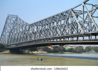KOLKATA, INDIA - MARCH 13: Fisherman boat crosses the Hooghly River nearby the Howrah Bridge on March 13, 2013. Hooghly Bridge is a famous landmark in the city of Calcutta / Kolkata, India.