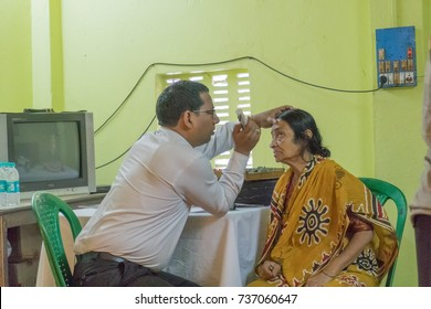 KOLKATA , INDIA - MARCH 19, 2017 : Male Doctor eye specialist checking eye sight of adult female sitting on a chair, at a free public eye testing camp. Editorial stock image.