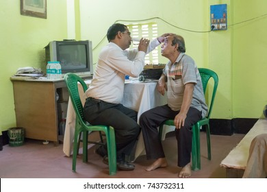 KOLKATA , INDIA - MARCH 19, 2017 : Male Doctor eye specialist checking eye sight of adult male sitting on a chair, at a free public eye testing camp. Editorial stock image.