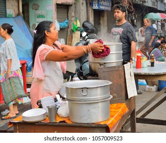 Kolkata, India - March 25, 2017: A woman selling momo in a roadside stall.