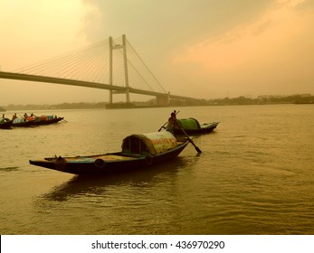 Kolkata, India - May 01, 2016: A fisherman rides across the river ganges in the midst of a dust storm during sunset.