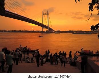 Kolkata, India - May 06, 2017: People watching sunset over river ganges with Vidyasagar setu bridge in the background.