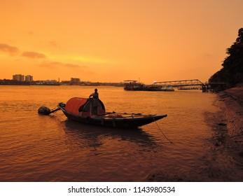 Kolkata, India - May 06, 2017: Country boat sailing in river Hooghly during sunset.