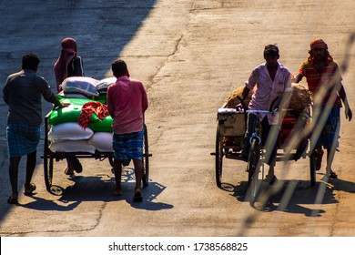 Kolkata, India - May 2020: Lockdown for COVID-19 - Two loaded cycle vans being pulled by laborers