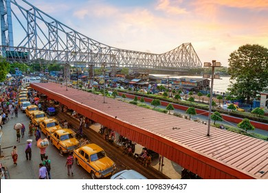 Kolkata, India, May 25,2018: Historic Howrah bridge with view of city road with yellow cabs in queue as seen from Howrah railway station Kolkata at sunrise.