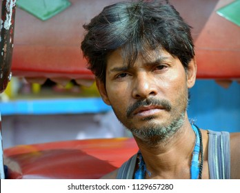 KOLKATA, INDIA - NOV 10, 2016: Young West Bengali rickshaw puller sits on the footwell of his human-drawn rickshaw, waits for a passenger and poses for the camera, on Nov 10, 2016.