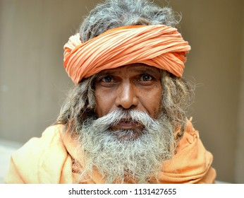 KOLKATA, INDIA - NOV 11, 2016: Bearded Indian Hindu <i>sadhu</i> wears an orange robe with orange head wrap and poses for the camera, on Nov 11, 2016.