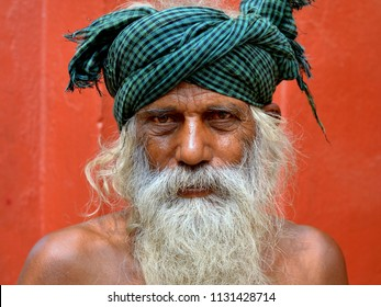 KOLKATA, INDIA - NOV 11, 2016: Old Indian beggar with a lived-in face and long white beard wears a checkered head wrap and poses for the camera, on Nov 11, 2016.