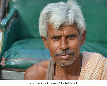 KOLKATA, INDIA - NOV 12, 2016: West Bengali rickshaw puller rests on the footwell of his human-drawn rickshaw, waits for a passenger and poses for the camera, on Nov 12, 2016.