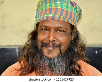 KOLKATA, INDIA - NOV 12, 2016: Smiling Indian beggar and sadhu (Hindu holy man) with thick beard and unkempt long hair wears a checkered head wrap and poses for the camera, on Nov 12, 2016.