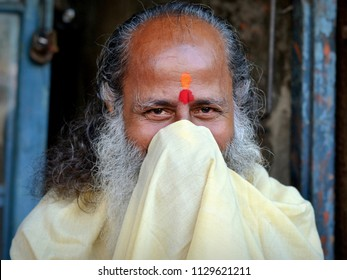 KOLKATA, INDIA - NOV 7, 2016: Elderly Hindu priest with two tilaka marks on his forehead blows his nose with his priest's robe and smiles at the camera, on Nov 7, 2016.