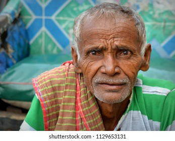 KOLKATA, INDIA - NOV 8, 2016: Old West Bengali rickshaw puller rests on the footwell of his human-drawn rickshaw, waits for customers and poses for the camera, on Nov 8, 2016.