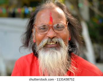 KOLKATA, INDIA - NOV 9, 2016: Smiling, old Indian sadhu with eyeglasses and red tilaka on his forehead poses for the camera, on Nov 9, 2016.