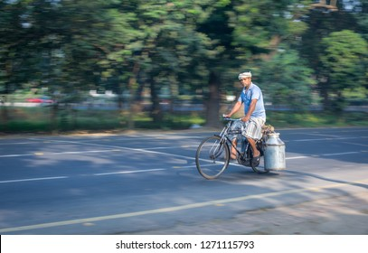 KOLKATA, INDIA - NOVEMBER 13, 2018 : A MILKMAN CYCLING THROUGH RED ROAD IN A COLD WINTER MORNING
