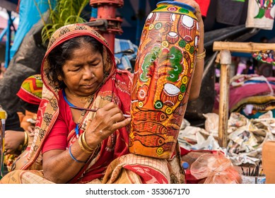KOLKATA, INDIA - NOVEMBER 28: An Indian elderly craftswoman paints on colorful handicraft items for sale during the annual State Handicrafts Expo 2015 on November 28,2015 in Kolkata,West Bengal,India