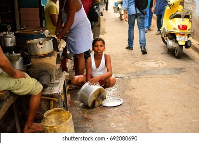 Kolkata, India - October 01, 2016: A child washing utensils in the street.