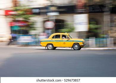 KOLKATA, INDIA - OCTOBER 20, 2016: Yellow cab in Kolkata driving fast through Park Street