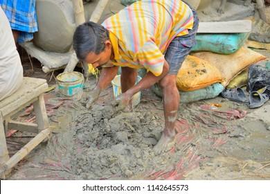 Kolkata, India - October 23, 2016: A man mixing clay for idol preparation by the roadside.