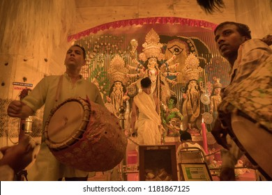 KOLKATA , INDIA - SEPTEMBER 27, 2017 : Young Dhaakis (drummers) performing - Durga Puja festival ritual. - shot at night under colored light. Biggest festival of Hinduism.