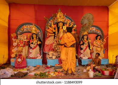 "KOLKATA , INDIA - SEPTEMBER 27, 2017 : Hindu Priest worshipping Goddess Durga with hand fan and bell - ritual called ""Durga aarti"", Durga Puja festival . Biggest festival of Hinduism ."