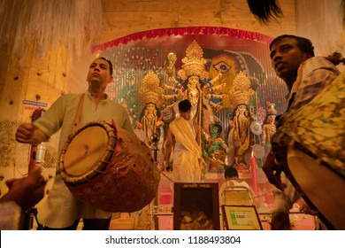 KOLKATA , INDIA - SEPTEMBER 27, 2017 : Young Hindu Priest worshipping Goddess Durga under holy smoke with dhaakis (drummers) performing. Durga Puja - shot at night under colored light .