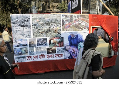 KOLKATA - JANUARY 24:A woman passing a vehicle which has the war atrocities images to protest Obama's three day visit India to attend India�s Republic Day parade on January 24, 2015 in Kolkata, India.