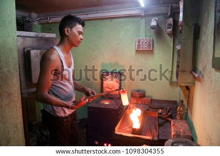 KOLKATA- JUNE 8: Ranjit- A worker melting solid gold while manufacturing gold chains or necklaces in India-the largest consumer of gold on 8th June, 2015 in Kolkata, India.