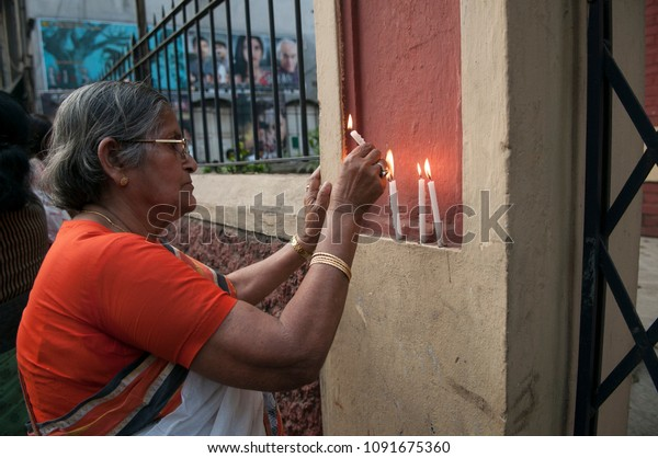 KOLKATA - MARCH 18: An old woman lighting a candle in front of a church  during a rally to protest gang rape of a 70 year old nun in Kolkata, India on March 18, 2015