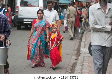 KOLKATA- MARCH  27: A girl child coming back home with her mother after the Kumari (young unmarried Hindu girl) Puja festival in Adyapith near Kolkata on 27th March, 2015.