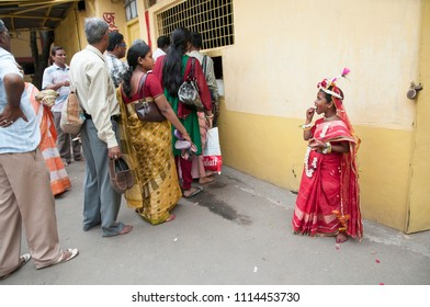 KOLKATA- MARCH  27: A girl child waiting while elders line up to take coupons for food during Kumari (young unmarried Hindu girl) Puja festival in Adyapith near Kolkata on 27th March, 2015.