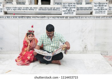 KOLKATA- MARCH  27: A girl waiting outside while her father is going through a newspaper during Kumari (young unmarried Hindu girl) Puja festival in Adyapith near Kolkata on 27th March, 2015.